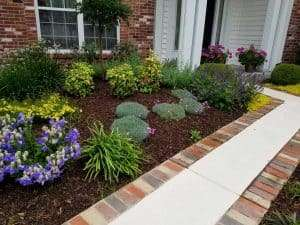 A front walkway is edged with bricks and flowers by Passiglia's