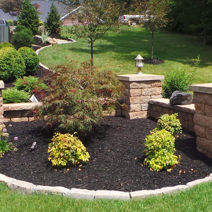 A planting bed edged in stone with mulch